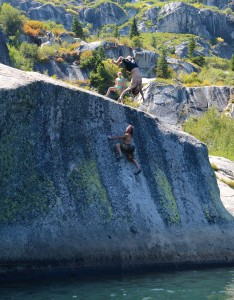 "Isaac Caldiero backflips while Dave Hatchett climbs ""Crystal Clear"" v2/3 at Anogora Lakes."